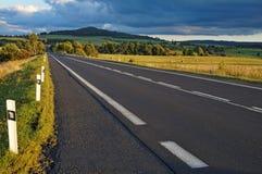 Asfaltväg till och med fälten in mot horisonten Royaltyfri Fotografi