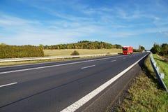 Asfaltvägen med annalkande lastbilar i bygd, den tidiga hösten färgar Royaltyfria Bilder