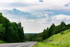 Asfaltvägen med teckning, en slingrig huvudväg lokaliseras mellan träd och en kulle med grönt gräs arkivfoton