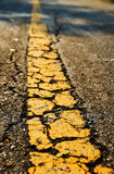 Asfaltvägen texturerar med det gula band Arkivbilder