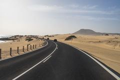 Asfaltvägen till och med sanddyerna Arkivfoton