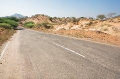 Asfaltväg i ökenområde Arkivfoto