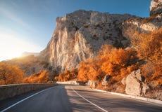 Asfaltweg in bergen bij zonsopgang in de herfst royalty-vrije stock afbeeldingen