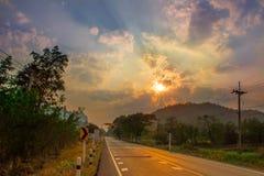 Asfaltweg buiten de stad bij zonsondergang Royalty-vrije Stock Fotografie