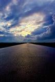 Asfaltweg en donkere donderwolken over het royalty-vrije stock afbeeldingen