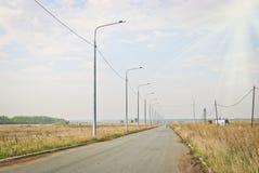 Asfaltweg en lantaarns aan de kant van de weg en een eenzame fietser in de afstand in de warme zonneschijn stock fotografie