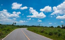 Asfaltweg en wolken op blauwe hemel Stock Fotografie
