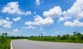 Asfaltweg en wolken op blauwe hemel Royalty-vrije Stock Foto