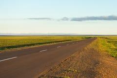 Asfaltweg met het landschapsachtergrond van de zonsondergangaard Stock Foto