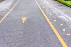 Asfaltweg met twee gele lijnen en de samenvatting van het stoepteken op achtergrond stock foto