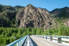 Asfaltweg op de achtergrond van de Sayan-bergen in de zomer Stock Fotografie