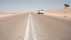 Asfaltweg rechtstreeks in de woestijn in het zuiden van Oman met een geparkeerd 4x4-voertuig stock foto's