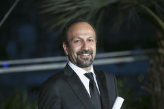 Asghar Farhadi poses with his award for the Best Screenplay. Asghar Farhadi poses with his award  for the film `The Salesman Forushande` at the Palme D`Or Winner Royalty Free Stock Photos