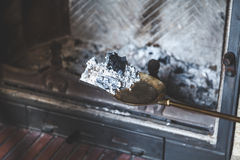 Ash from fire lay extinguished on brass blade Stock Image