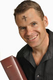 Ash Wednesday. Smiling man with mark of ashes on forehead holds holy Bible royalty free stock photography