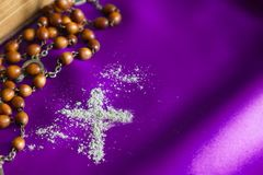 Ash Wednesday religion concept on violet fabric background with rosary royalty free stock image