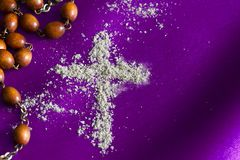 Ash Wednesday religion concept on violet fabric background with rosary. Closeup stock photography