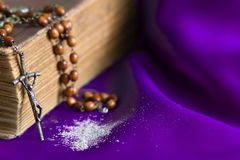 Ash Wednesday religion concept on violet fabric background with rosary. Closeup stock image