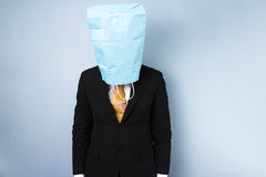 Ashamed businessman with bag over his head. Ashamed businessman with a paper bag over his head Stock Photography