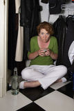 Ashamed Closet Drinker. Ashamed woman hidding in the closet holding a drink with an open bottle royalty free stock image