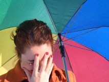 Ashamed girl. A shy girl with a rainbow umbrella Stock Photography