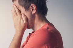 Ashamed man covering face Stock Photography