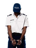 Ashamed policeman with handcuffs Royalty Free Stock Images
