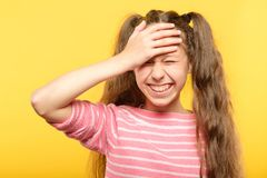Ashamed smiling girl cover forehead hand embarrass. Ashamed smiling girl covering her forehead with a hand. embarrassment and shame emotion stock images