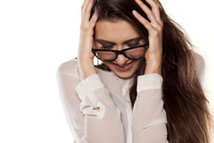 Ashamed and smiling. Ashamed smiling young woman with eyeglasses posing on a white background royalty free stock image