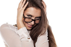 Ashamed and smiling. Ashamed smiling young woman with eyeglasses posing on a white background stock photo