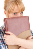 Ashamed young woman with book Stock Image