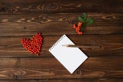 Ashberry als hartvorm bij de lijst en het potlood op notitieboekje: houten achtergrond Royalty-vrije Stock Afbeelding
