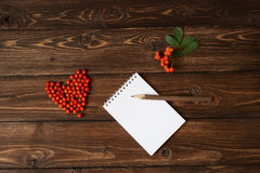 Ashberry as a heart shape at the table and pencil on notebook: wooden background. Ashberry as a heart shape at the table and hand-made pencil on notebook: wooden Royalty Free Stock Image