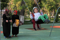 Ashgabad, Turkmenistan - October 9, 2014: Two women in Iranian c. Lothes with children in the park Royalty Free Stock Image