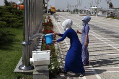 Ashgabat, Turkmenistan - Februari 26, 2013 Vrouwen belast met de mens Stock Fotografie