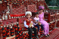 Ashgabat, Turkmenistan - September, 12, 2017. Unknown Turkmen family with children. Boy in traditional national clothes. stock photo