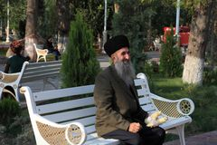 Ashgabat, Turkmenistan - October 10, 2014. Elderly smiling man s. Itting on a bench in the park Royalty Free Stock Photos