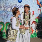 ASHGABAT, TURKMENISTAN -  January, 04, 2017: Two unknown young girls in national clothes laugh and talk. ASHGABAT, TURKMENISTAN -. January, 04, 2017 Royalty Free Stock Photo