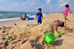 Ashkelon - Israel. ZIKIM,ISR - July 07:Children bury their father in sand near Rutenberg Power Station on July 07 2011.It's the newest thermal power station in stock images