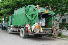 Ashman loads garbage into a truck Stock Photo
