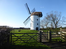 Windmill in field behind gate Royalty Free Stock Images