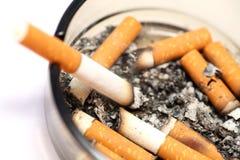 ashtray εθισμού τα κακά τσιγάρα ανασκόπησης κλείνουν το σκοτάδι επάνω Στοκ Φωτογραφία