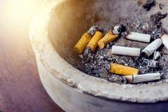 ashtray εθισμού τα κακά τσιγάρα ανασκόπησης κλείνουν το σκοτάδι επάνω Ashtray και τσιγάρα Στοκ Εικόνες
