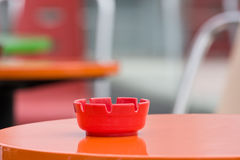 The ashtray. Red ashtray on an empty red table on a terrace Royalty Free Stock Photos