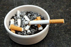Ashtray with butts and burning cigarette. Small roll of finely-cut tobacco leaves wrapped in a cylinder of thin paper for smoking Stock Photos