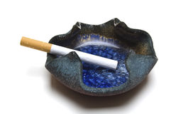 Ashtray with cigarette. An ashtray with a cigarette isolated on a white background Stock Photos