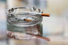 Ashtray with cigarette. On a reflecting surface of a glass table in a cafe stock photo