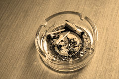 Ashtray with a cigarette butt. Sepia. Stock Photography