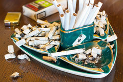 Ashtray with cigarette butts. An ashtray full of cigarette butts and ash Stock Image