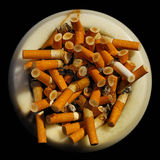 Ashtray with cigarette butts. Overhead view of an ashtray completely filled with cigarette butts royalty free stock photography